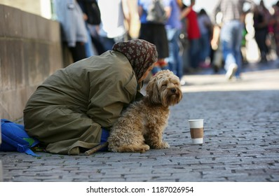 Prague, Czech Republic, September 17, 2018. Old beggar woman with dog begging on the Charles Bridge