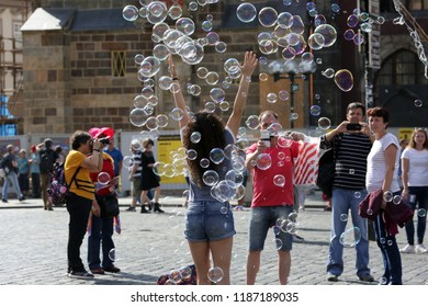 Prague, Czech Republic, September 17, 2018. Happy tourists on Prague Street, a man taking pictures of a woman among soap bubbles