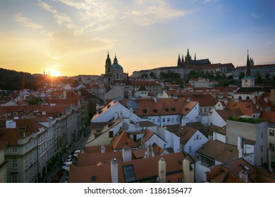 Prague, Czech Republic, September 19, 2018. Beautiful view from above on the city, roofs of houses, church st. Nicholas and Pradsky Castle at sunset