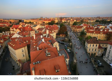 Prague, Czech Republic, September 19, 2018. Beautiful view from above on the city, red roofs of houses and Charles Bridge in the evening light