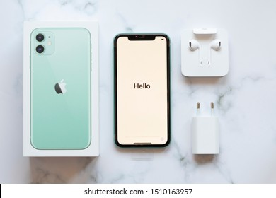 """Prague / Czech Republic - September 20 2019: Brand new mint iPhone 11 unboxed flat lay with box, iPhone turned on saying """"Hello"""", ear pods and power plug"""