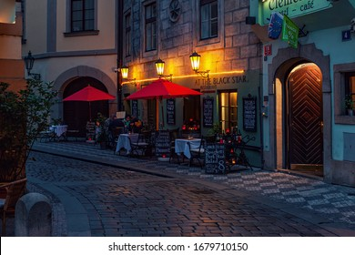 PRAGUE, CZECH REPUBLIC - SEPTEMBER 22, 2015: Small outdoor restaurant on evening cobblestone street in Old Town of Prague - capital and largest city of Czech Republic, popular tourist destination.