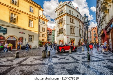 Prague, Czech Republic - September 25 2017: Tourists sightsee, shop and enjoy the cafes as they pass by a vintage red automobile in a picturesque section of Old Town Prague, Czech Republic.