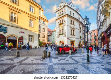 Prague, Czech Republic - September 25 2018: Tourists sightsee, shop and enjoy the cafes as they pass by a vintage red automobile in a picturesque section of Old Town Prague, Czech Republic.