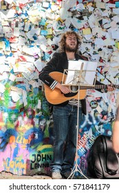 PRAGUE, CZECH REPUBLIC - September 25, 2014: Street Busker performing Beatles songs in front of John Lennon Wall on Kampa Island. Busking is legal form of earning money on Praha Streets.