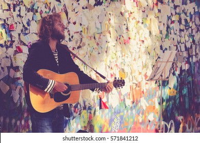 PRAGUE, CZECH REPUBLIC - September 25, 2014: Vintage photo of street Busker performing Beatles songs in front of John Lennon Wall. Busking is legal form of earning money on Praha Streets.