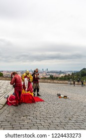 PRAGUE, CZECH REPUBLIC - SEPTEMBER 26, 2014: Three male street performers in traditional medieval clothing outdoors on a cobblestone square next to Prague castle in Prague September 26, 2014.
