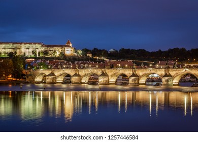 PRAGUE, CZECH REPUBLIC - SEPTEMBER 26, 2014: Beautiful night view by the water with people on illuminated Charles Bridge and Prague Castle in the background in Prague Czech Republic September 26, 2014