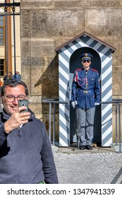 Prague, Czech Republic - September 26, 2018: Unidentified tourists are photographed with the guards at the gates of Prague Castle.