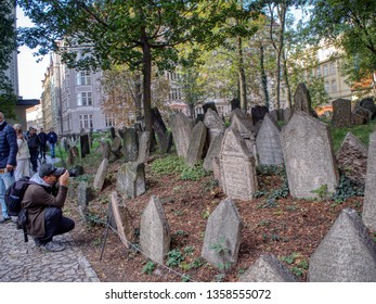 Prague, Czech Republic - September 26, 2018: Tombstones on Old Jewish Cemetery in the Jewish Quarter in Prague.There are about 12000 tombstones presently visible. Man photographing the headstones