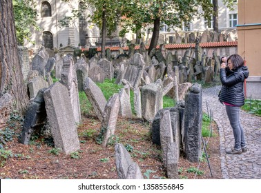 Prague, Czech Republic - September 26, 2018: Tombstones on Old Jewish Cemetery in the Jewish Quarter in Prague.There are about 12000 tombstones presently visible. Woman photographing the headstones