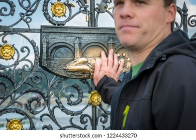 PRAGUE, CZECH REPUBLIC - SEPTEMBER 27, 2014: Closeup frontview with selective focus of a male holding his hand against a decorative bronze plaque on a fence in Prague Czech Republic September 27, 2014