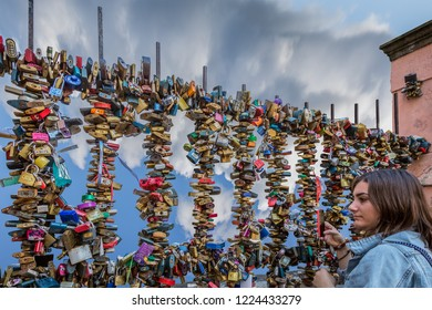 PRAGUE, CZECH REPUBLIC -SEPTEMBER 27, 2014: Closeup sideview of a young woman taking a photo of many colorful padlocks on a steel fence outdoors in Prague Czech Republic September 27, 2014.