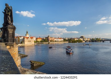 PRAGUE, CZECH REPUBLIC - SEPTEMBER 27, 2014: Cityscape view of a cruise ship seen from Charles bridge with a statue in the foreground and city in the background in Prague September 27, 2014.