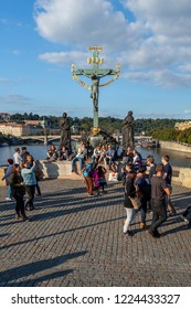 PRAGUE, CZECH REPUBLIC - SEPTEMBER 27, 2014: Front view of a group of people resting and taking photos in front of a Christ statue on Charles bridge in Prague Czech Republic September 27, 2014.