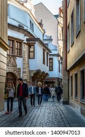 PRAGUE, CZECH REPUBLIC - SEPTEMBER 27, 2014: Front street view of people walking on a narrow cobblestone street in the Old Town of Prague Czech Republic September 27, 2014.