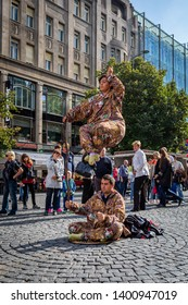 PRAGUE, CZECH REPUBLIC - SEPTEMBER 27, 2014:  Levitating illusion act of a male and female street performer on a cobblestone square with people looking in Prague Czech Republic September 27, 2014.