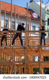 PRAGUE, CZECH REPUBLIC - SEPTEMBER 27, 2014: Outdoor closeup of three male carpenters building a wooden frame structure in Prague Czech Republic September 27, 2014.