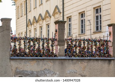 PRAGUE, CZECH REPUBLIC - SEPTEMBER 27, 2014: Front view of people on a stone bridge behind a steel fence with many padlocks in Prague Czech Republic September 27, 2014.