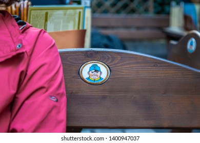 PRAGUE, CZECH REPUBLIC - SEPTEMBER 27, 2014: Closeup of a womans arm and a small sign on a wooden bench. Sign of the national Czech character The Brave Soldier Svejk in Prague September 27, 2014.