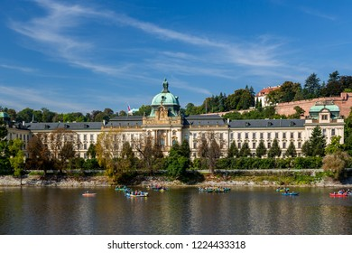 PRAGUE, CZECH REPUBLIC - SEPTEMBER 28, 2014: Front view of Straka Academy, Government of Czech Republic. Waterside with many people canoeing on the river in the foreground, Prague September 28, 2014.