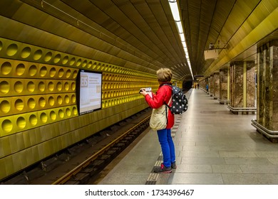 PRAGUE, CZECH REPUBLIC - SEPTEMBER 28, 2014: Perspective view of a woman with backpack looking at a decorated golden wall at an underground subway station in Prague Czech Republic September 28, 2014.