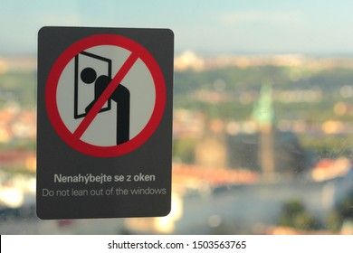 "Prague, Czech Republic - September 4, 2019: Sticker on Petrin Tower saying ""Do not lean out of the windows"" with the Prague Castle in the background."