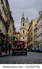 Prague, Czech Republic - September 8, 2018 - Vintage car and St. Nicholas Church at the end of the street Malá Strana