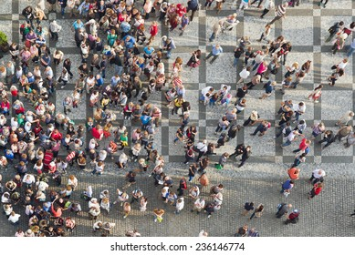 PRAGUE, CZECH REPUBLIC - SEPTEMBER 9, 2014: Top View of Large group of tourists at city central square looking up to Old Town Hall tower.