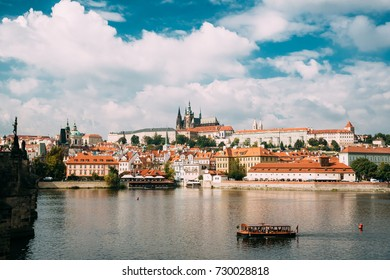 Prague, Czech Republic. Sightseeing Boat Sailing Along Vltava River On Background Upper Town. Prague Castle And Metropolitan Cathedral Of Sts Vitus, Wenceslaus And Adalbert. UNESCO World Heritage Site