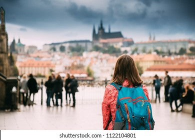 Prague, Czech Republic. Young Caucasian Woman Backpacker Looking At Upper Town On Background. Prague Castle And Metropolitan Cathedral Of Sts Vitus, Wenceslaus And Adalbert. UNESCO World Heritage Site