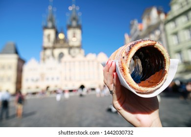 Prague, Czech Republic.Caucasian tourist woman holding and tasting tradition Czech sweet cookie (trdelnik) in the centre old town Prague on Tyn church background.