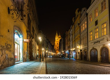 Prague, Czech Republic-February 02, 2019. Night view of old street from the Lesser Town Tower of Charles Bridge leading to the Mala Strana square at old part of Prague town.