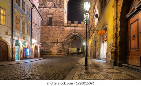 Prague, Czech Republic-February 02, 2019. Night street view of the entrance through Lesser Town Tower of Charles Bridge from Mala Strana square at old part of Prague town.