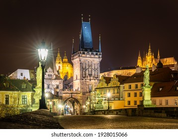 Prague, Czech Republic-January 31, 2019. Night view of the famous, historical Charles Bridge over the Vltava river, The Lesser Town Bridge Tower and Prague Castle on the hill in old Prague town.