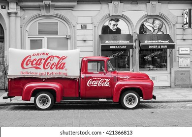 PRAGUE, CZECH REPUBLIC-MAY 15: a red retro car Ford F-100 with advertising inscription Coca Cola on board on the streets of Prague's Old Town May 15, 2015