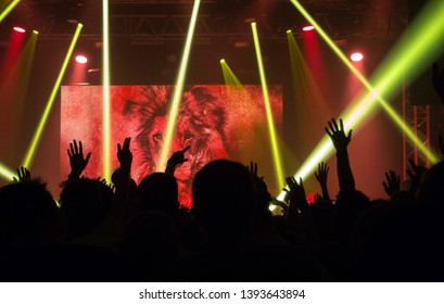 Prague, Czechia, November 9, 2016. Hands on concert. Audience with hands up at a music festival and lights and lasers streaming down from above the stage. A lot of people enjoying party and dancing.