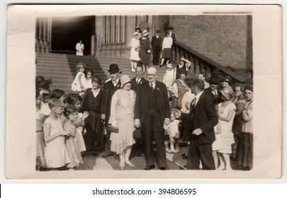 PRAGUE, THE CZECHOSLOVAK  REPUBLIC -  JUNE 28, 1930: Vintage photo shows elderly newlyweds in front of church after wedding ceremony. Black & white antique photography.