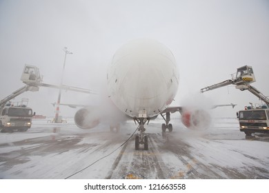 PRAGUE - DECEMBER 11: Ground crew of Czech Airlines Handling provides de-icing. They are spraying the aircraft, which prevents the occurrence of frost on December 11, 2012 in Prague, Czech Republic.