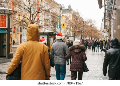 Prague, December 24, 2017: Christmas in Prague - unknown people in Santa Claus red caps walking along the street during Christmas holidays