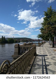 Prague Embankment, landscape, embankment on the banks of the Vltava River, wrought-iron lattice, sunny day, view of the bridge. European city in summer