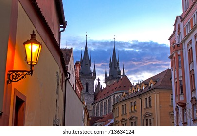 Prague evening scene - old lamp projecting golden light on the wall and medieval steeples of the Church of Our Lady before Týn on the background.