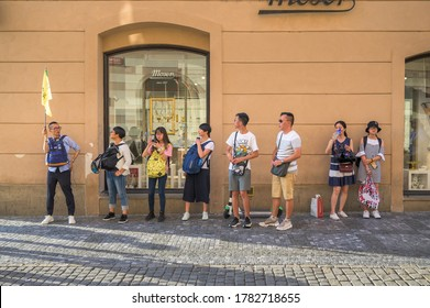 PRAGUE - JULY 20, 2019: Asian tourists lined up behind a flag carrying tour guide on the cobbled streets of The Old Town Quarter of Prague, Czech Republic