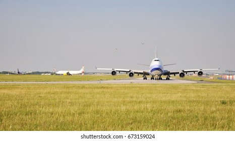 PRAGUE - July 6, 2017: Cargo China Airlines - Boeing 747-400F aircraft taxiing along the runway before departure from Prague Airport Vaclav Havel, Czech Republic. In background Vueling airline