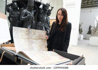 """PRAGUE - MAY 12, 2019: Book World Prague 2019. Woman looking through an exposed luxury book """"Epopej"""" reproductions of paintings by Alfonse Mucha. One of the most expensive czech book published"""