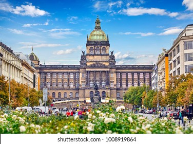 Prague national museum building at Wenceslas Square Czech Republic famous landmark in Europe tree and rose bushes blue sky with clouds.