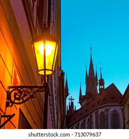 Prague night scene - old lamp projecting golden light on the wall and medieval steeples of the Church of Our Lady before Týn on the background.
