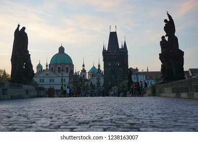 Prague old famous medieval Charles Bridge (Karluv most) at sunrise with very few people, in spring, with Old Town Bridge Tower in background and statues, the Czech Republic (Czechia)
