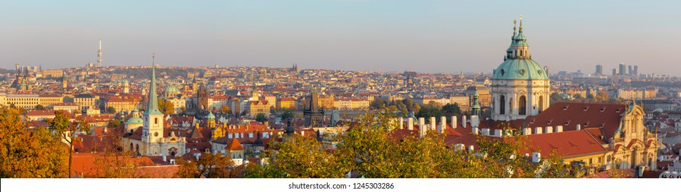 Prague - The panorama of Town with the St. Nicholas church and Charles bridge in evening light.