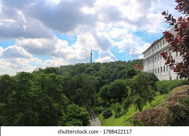 Prague Petrska tower (Petřínská rozhledna) surrounded by green trees against the background of clouds on a summer, hot, Sunny day.
